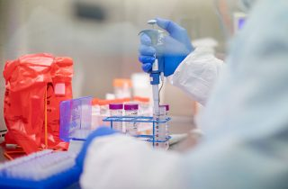 Coding COVID-19 Claims | A healthcare worker in protective gear conducts a lab test.