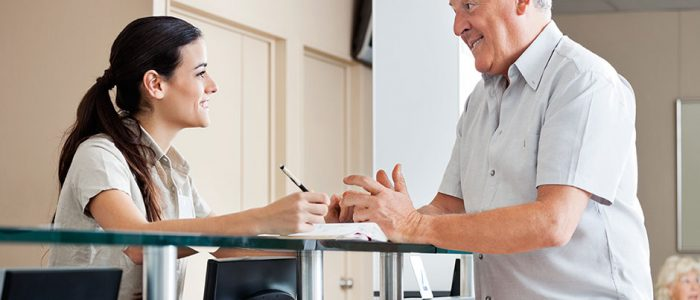 Improving Patient Satisfaction - Patient Talks to Receptionist at Check-in Desk