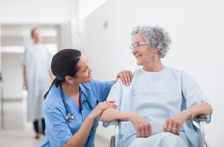Is There a Nursing Shortage? | Nurse Kneeling Down Talking to Patient in Wheelchair